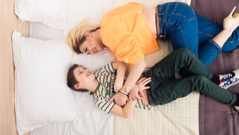 Mãe com o filho na cama, mãe e filho que têm o divertimento imagem de stock royalty free