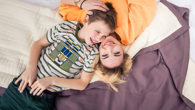Mãe com o filho na cama, mãe e filho que têm o divertimento imagem de stock