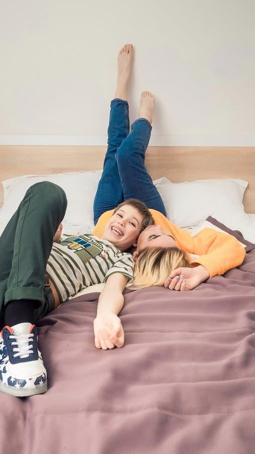 Mãe com o filho na cama, mãe e filho que têm o divertimento imagens de stock