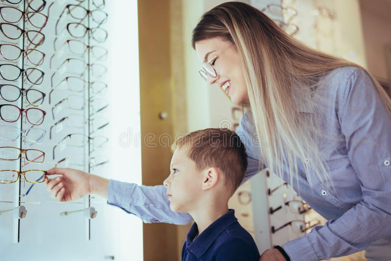 Mãe com o filho que escolhe vidros na loja do sistema ótico imagem de stock royalty free