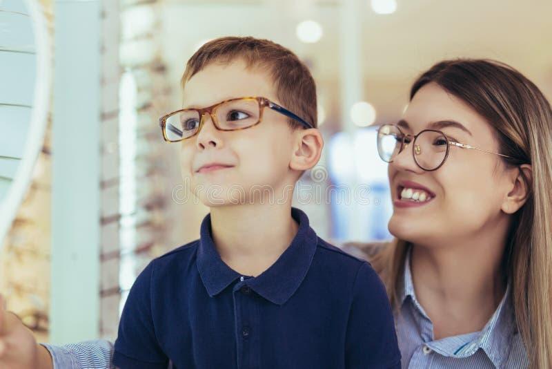 Mãe com o filho que escolhe vidros na loja do sistema ótico foto de stock royalty free