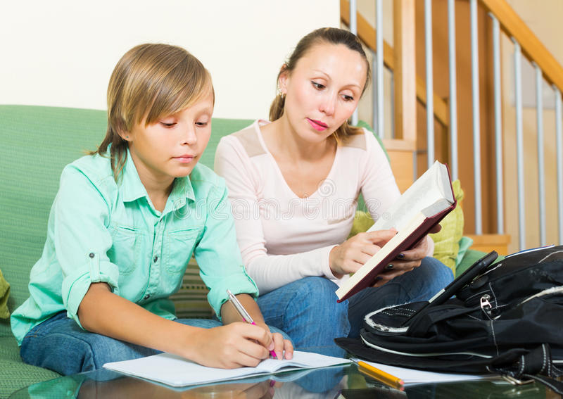 Mãe com o filho que faz trabalhos de casa imagem de stock