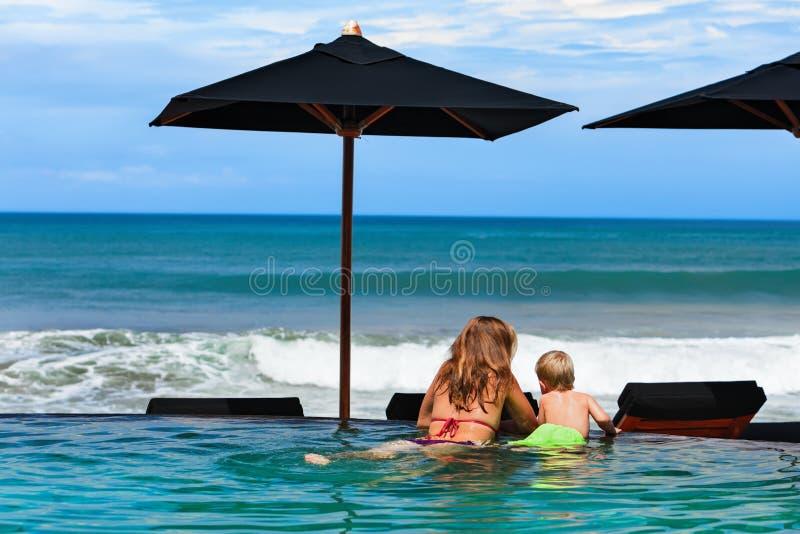 Mãe com o filho que refrigera na piscina da praia fotografia de stock