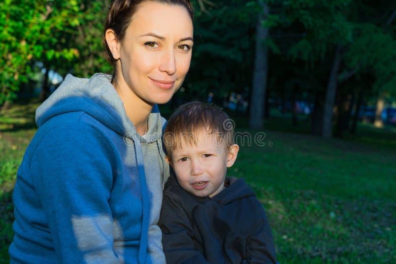 Mãe com o filho que senta-se na grama no parque fotos de stock