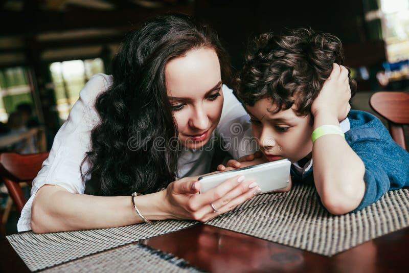 Mãe com o menino bonito pequeno que usa o telefone esperto junto no restaurante foto de stock