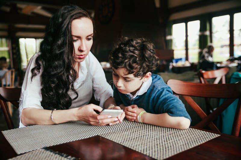 Mãe com o menino bonito pequeno que usa o telefone esperto junto no restaurante foto de stock royalty free