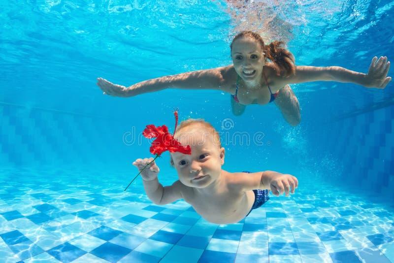 Mãe com o mergulho da criança subaquático na piscina fotos de stock royalty free