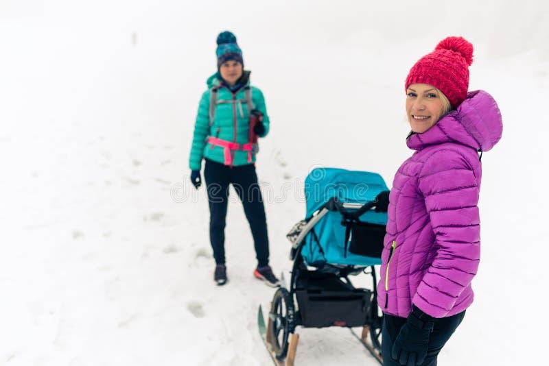 Mãe com o passeante de bebê que aprecia a floresta do inverno com amigo ou o sócio fêmea, tempo da família Mulher de passeio da c imagem de stock
