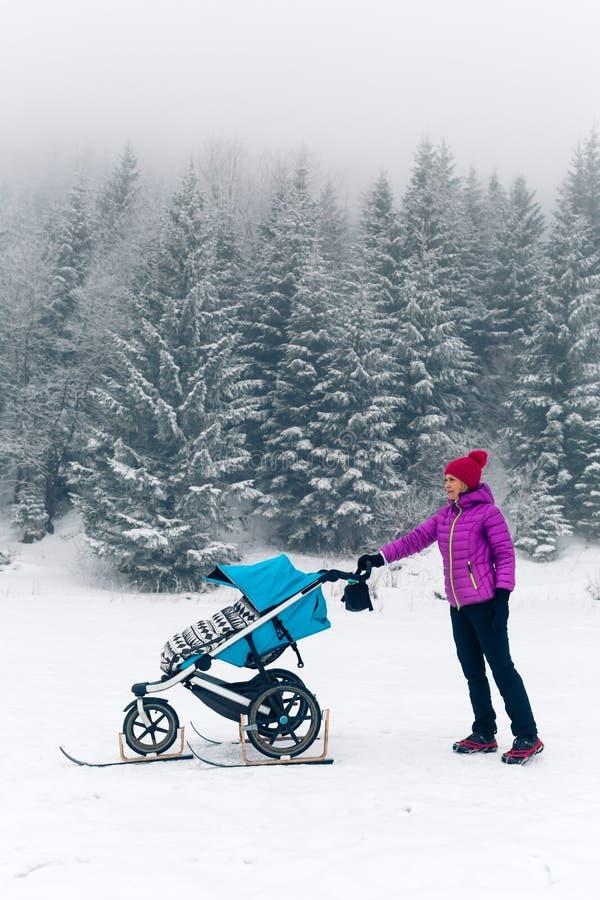 Mãe com o passeante de bebê que aprecia a maternidade na floresta do inverno fotos de stock royalty free