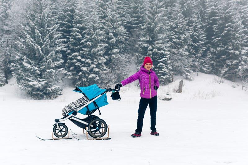 Mãe com o passeante de bebê que aprecia a maternidade na floresta do inverno imagens de stock royalty free