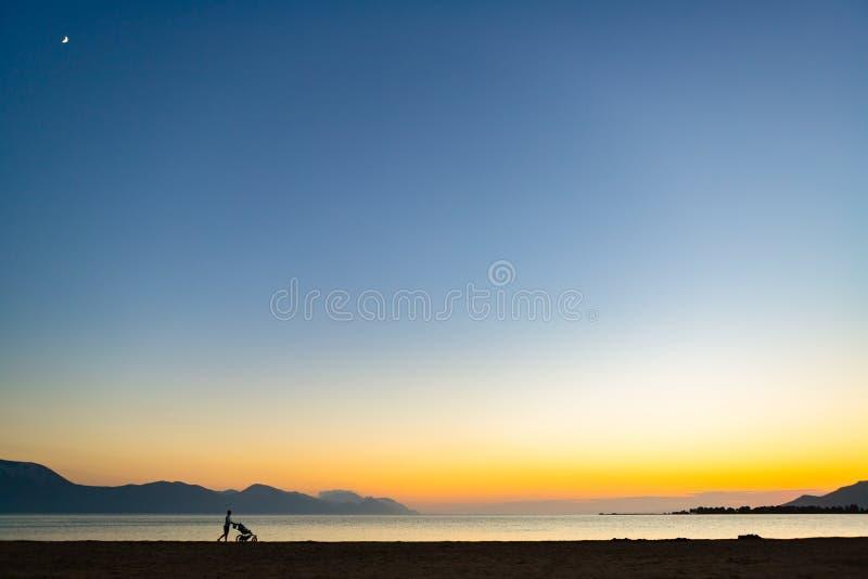 Mãe com o passeante de bebê que aprecia a maternidade no landscap do por do sol fotos de stock