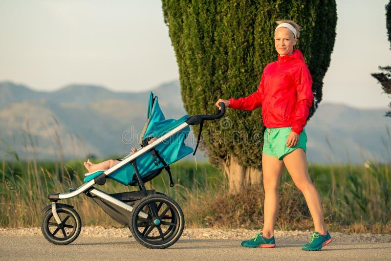 Mãe com o passeante de bebê que aprecia a paisagem do por do sol do verão imagem de stock royalty free