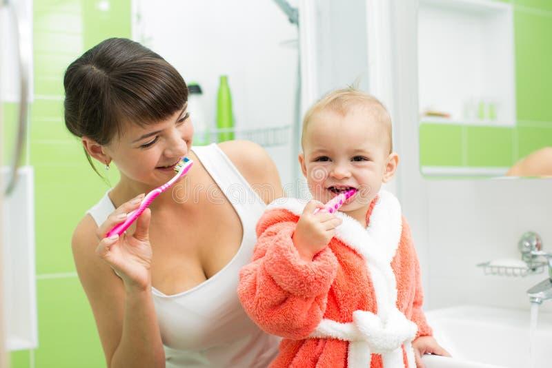 Mãe com os dentes de escovadela do bebê no banheiro foto de stock