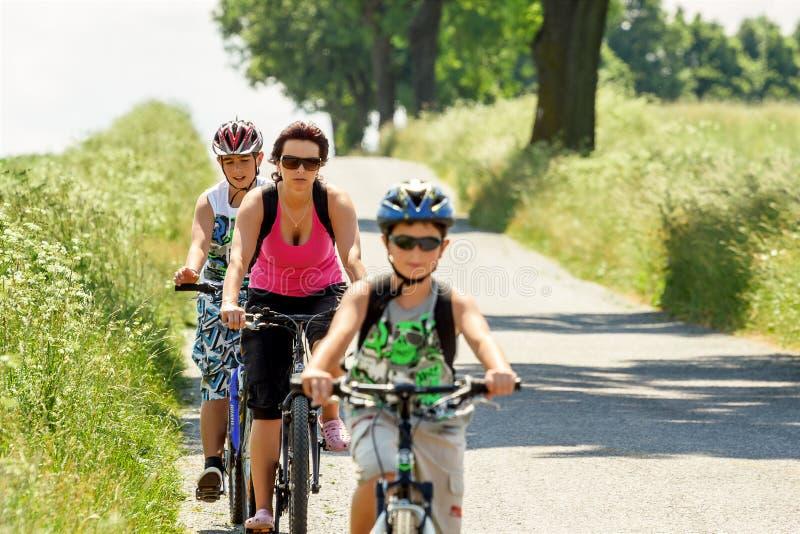 Mãe com os dois filhos na viagem da bicicleta imagens de stock