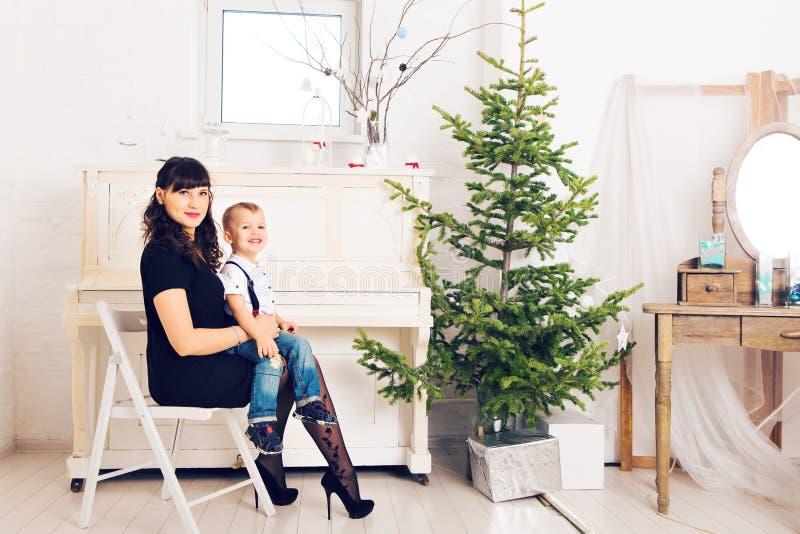 A mãe com seu filho que comemora feriados aproxima a árvore de Natal foto de stock