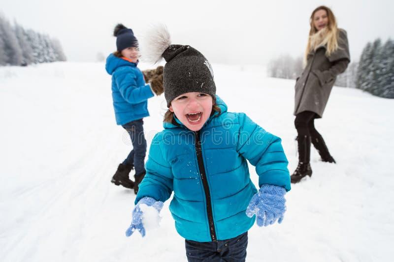Mãe com seu jogo exterior de dois filhos na neve fotografia de stock