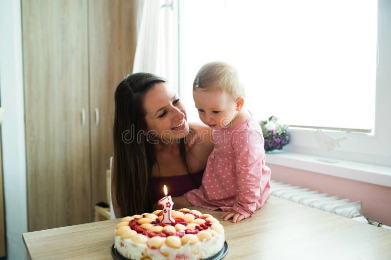 Mãe com seus filha e bolo de aniversário bonitos com vela foto de stock