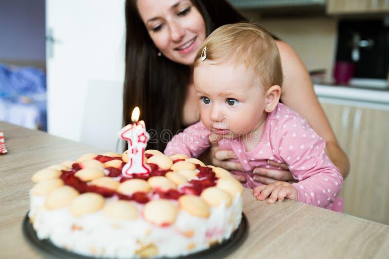 Mãe com seus filha e bolo de aniversário bonitos com vela fotografia de stock royalty free