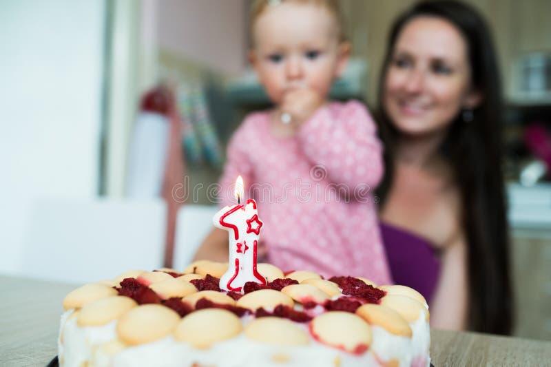 Mãe com seus filha e bolo de aniversário bonitos com vela fotos de stock