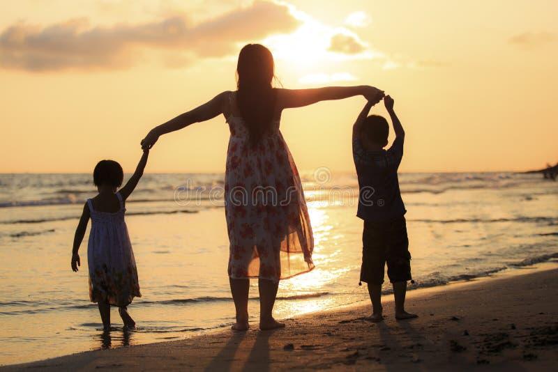 Mãe com seus filha e filho na praia fotografia de stock