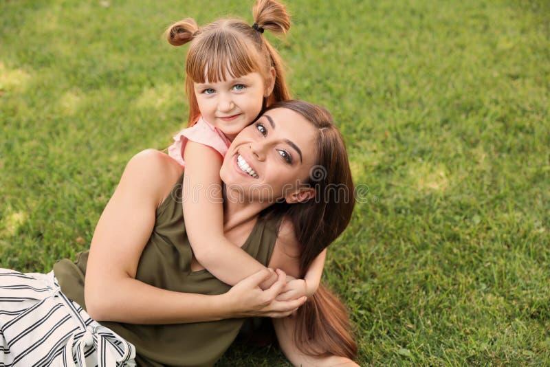 Mãe com sua criança bonito na grama verde imagem de stock