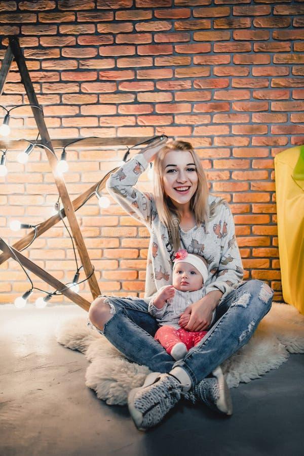 mãe com sua criança no fundo de uma estrela com bulbos foto de stock