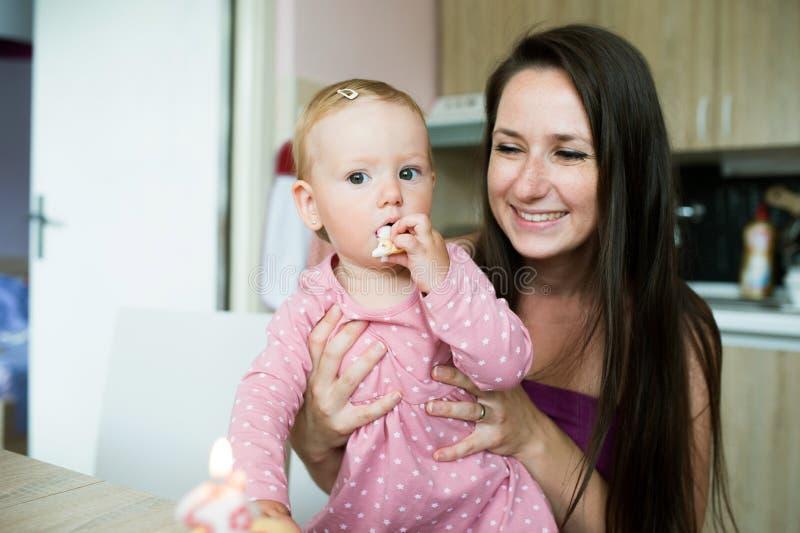 Mãe com sua filha bonito que come seu bolo de aniversário foto de stock