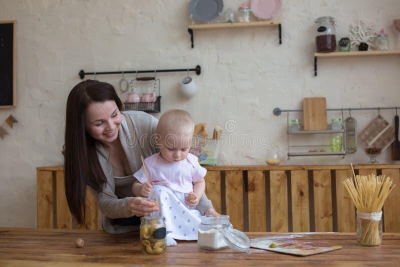 Mãe com sua filha do bebê na cozinha que cozinha junto, lifes fotografia de stock royalty free