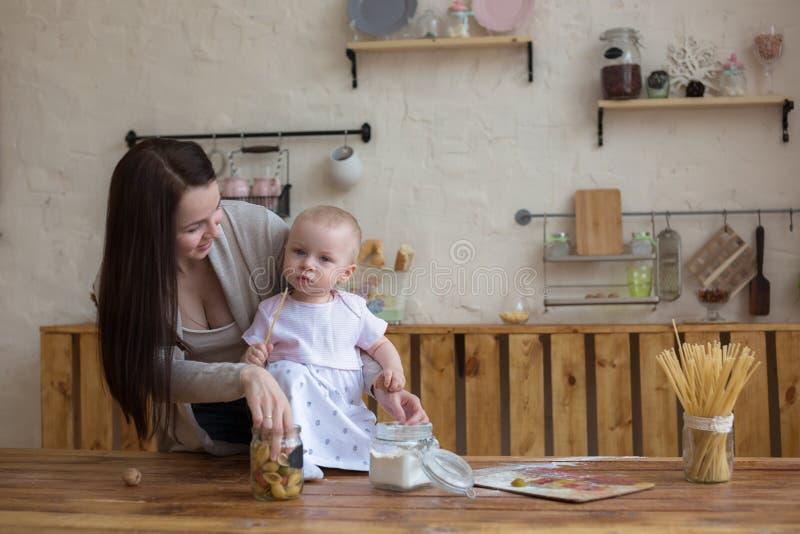 Mãe com sua filha do bebê na cozinha que cozinha junto, lifes imagens de stock royalty free