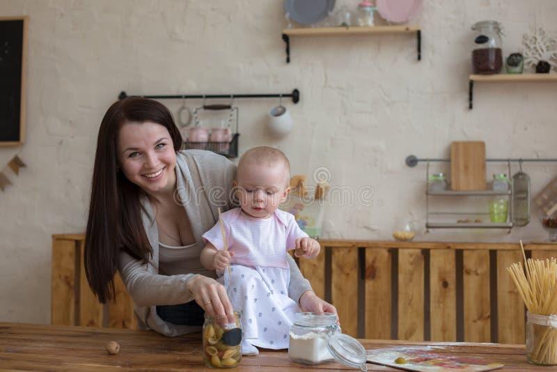 Mãe com sua filha do bebê na cozinha que cozinha junto, lifes foto de stock