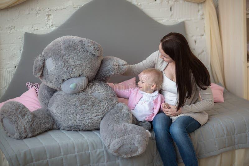 Mãe com sua filha do bebê que joga com o urso grande do brinquedo em um rea imagem de stock royalty free