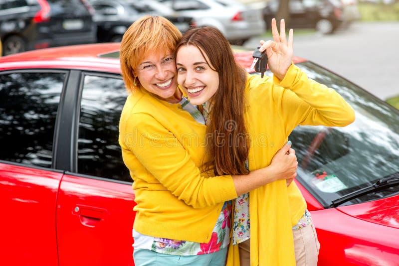 Mãe com sua filha perto do carro vermelho fotografia de stock
