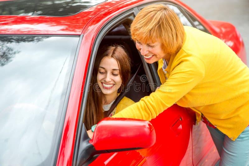Mãe com sua filha perto do carro vermelho fotos de stock