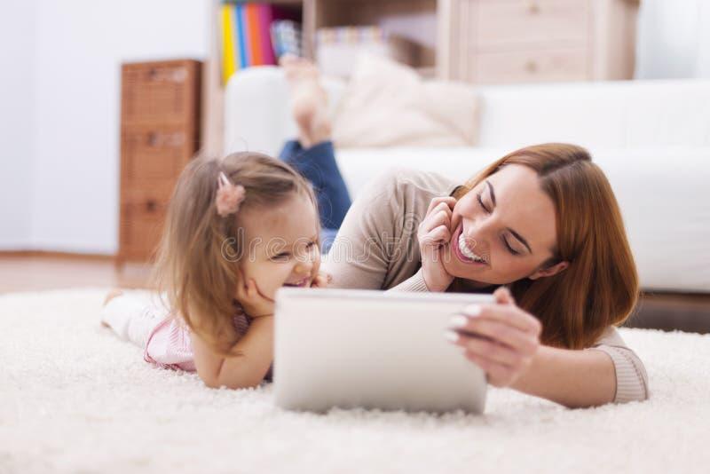 Mãe com sua filha que usa a tabuleta fotografia de stock
