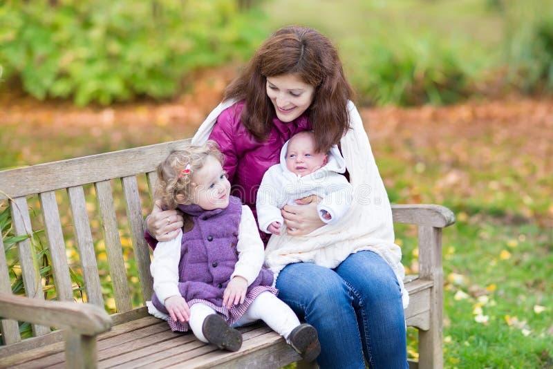 Mãe com suas crianças no banco de madeira no parque fotografia de stock