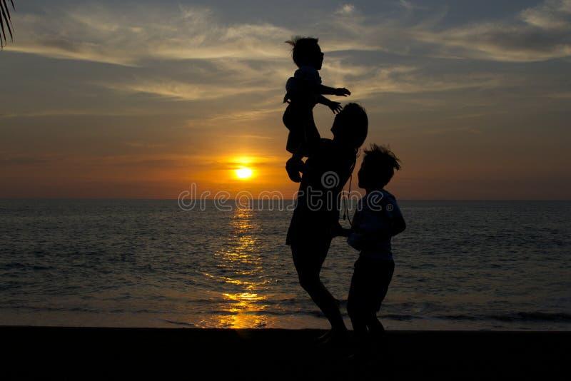 Mãe com suas crianças que jogam no por do sol fotos de stock royalty free