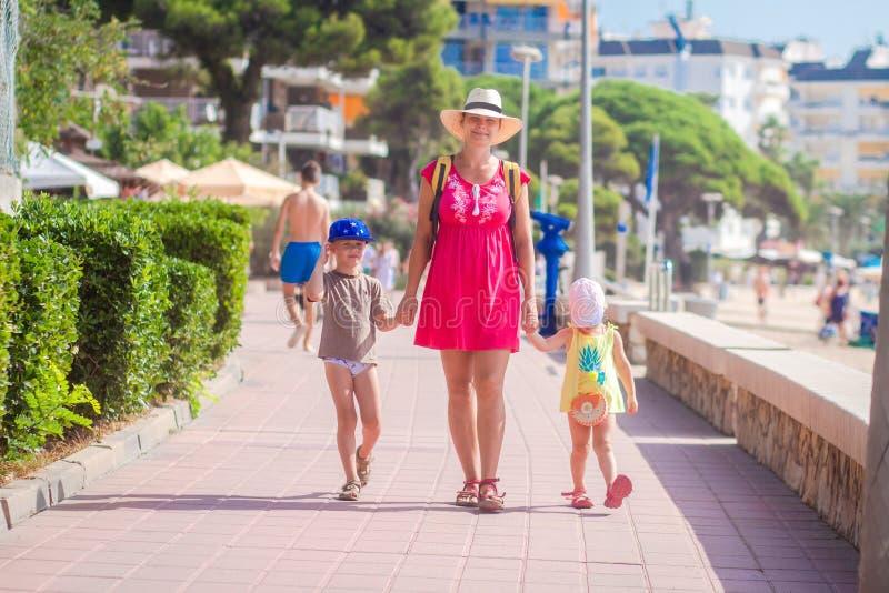 A mãe com suas crianças vai à praia do mar durante o resto tropical fotos de stock