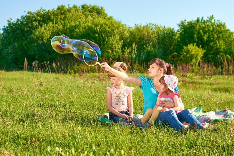 Mãe com suas duas filhas em um parque imagem de stock