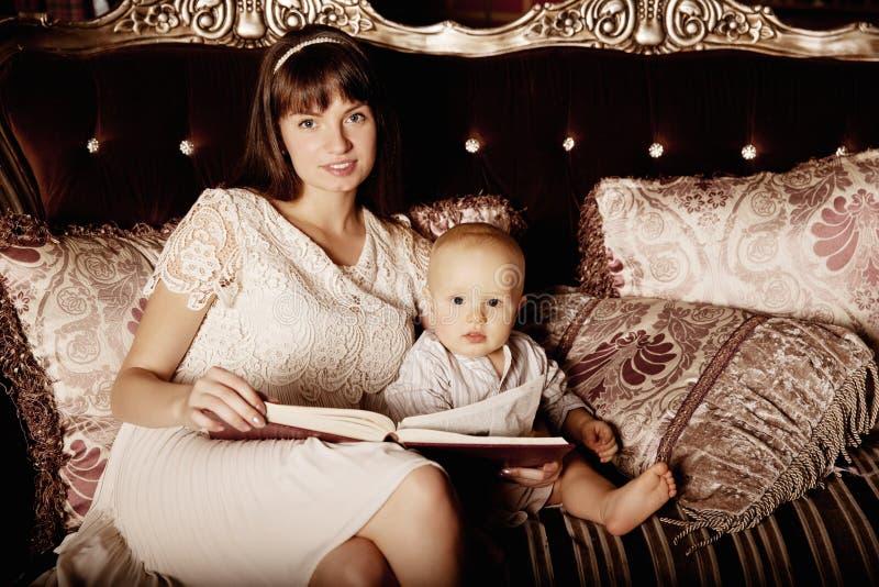 Mãe com uma criança pequena na leitura interior um togethe do livro fotografia de stock