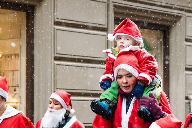 A mãe com uma criança pequena vestiu-se acima como Santa participam no evento Éstocolmo Santa Run da caridade na Suécia imagens de stock
