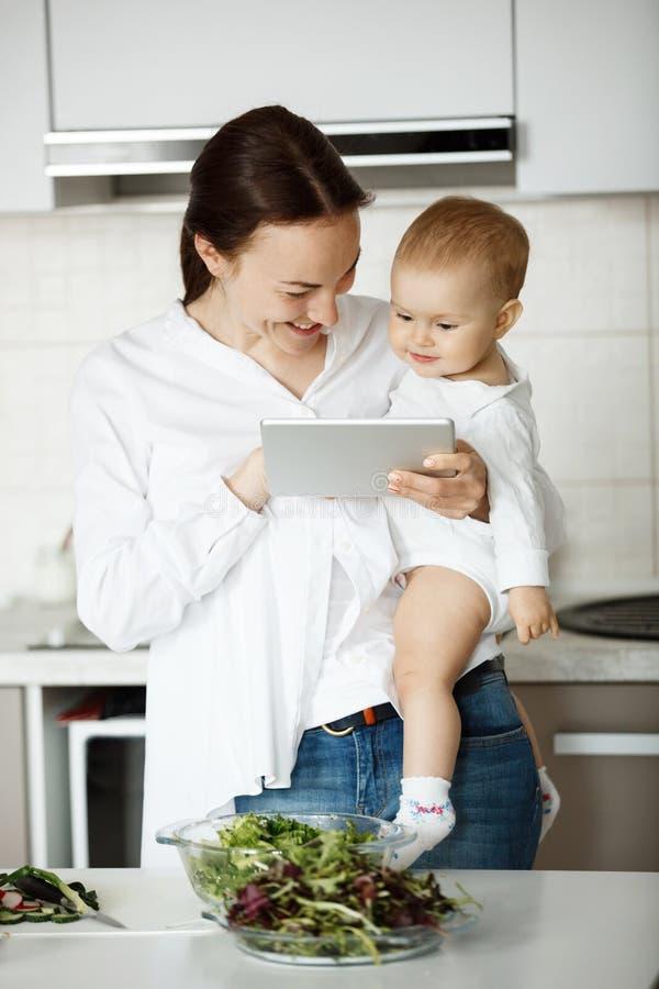 Mãe considerável alegre que guarda seu bebê pequeno precioso nas mãos, sorrindo e mostrando lhe desenhos animados na tabuleta dig fotos de stock royalty free