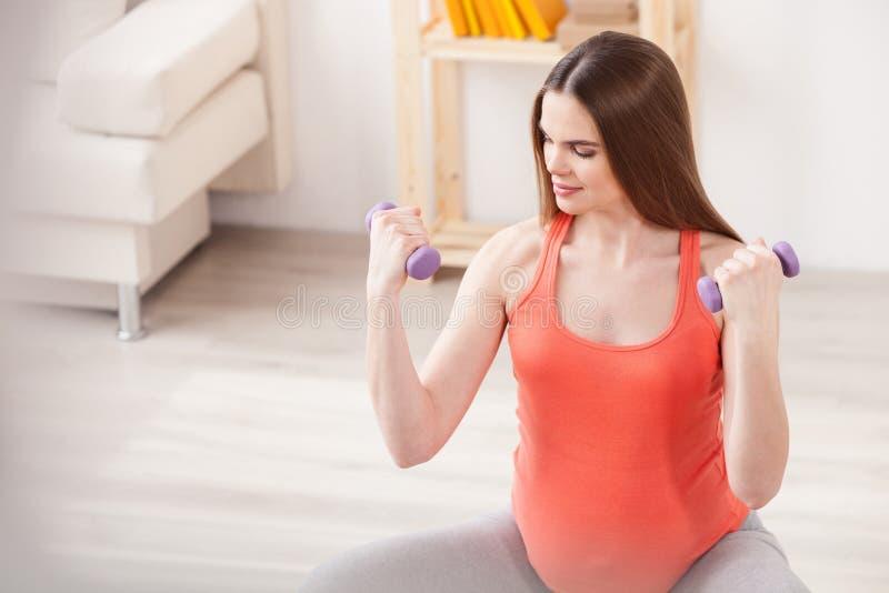 A mãe consideravelmente expectante está exercitando com pesos foto de stock royalty free