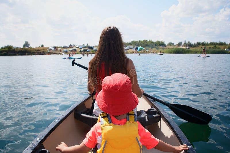Mãe consideravelmente nova e filho pequeno da criança que canoeing no lago foto de stock