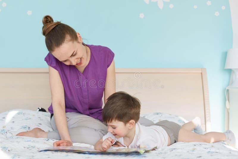 A mãe consideravelmente nova lê história de horas de dormir interessante a seu filho pequeno, pose junto na cama no quarto azul,  imagens de stock