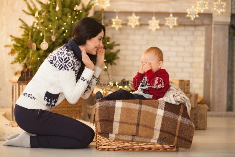 A mãe consola seu filho de grito pequeno no fundo da árvore de Natal imagens de stock royalty free