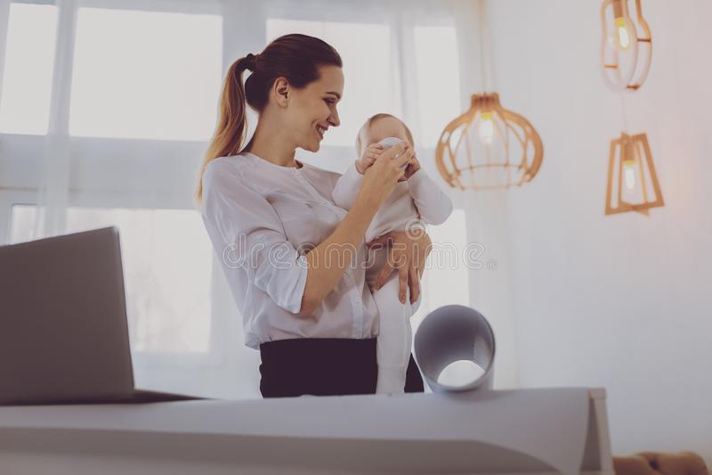 Mãe contente que ri quando seu leite bebendo do bebê pequeno imagens de stock
