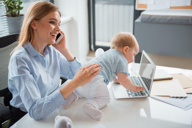 Mãe contente que trabalha com o bebê no escritório imagem de stock
