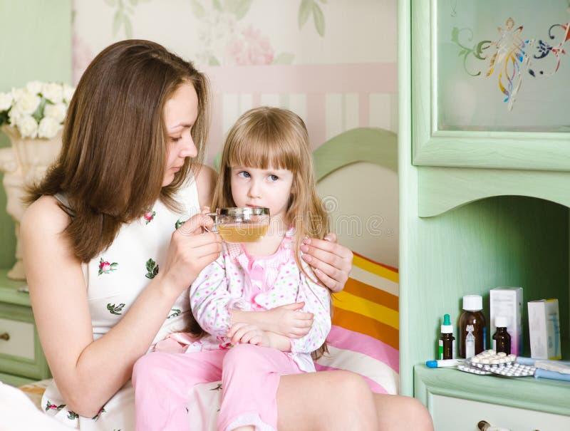 A mãe dá à bebida à criança doente fotografia de stock royalty free
