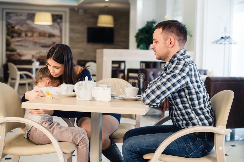 A mãe dá a consolação à filha de grito no restaurante e ao pai irritado foto de stock
