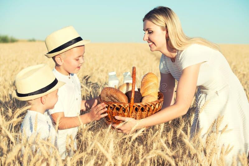 A mãe dá a crianças uma cesta com pão fresco e leite Um piquenique em um campo de trigo imagens de stock